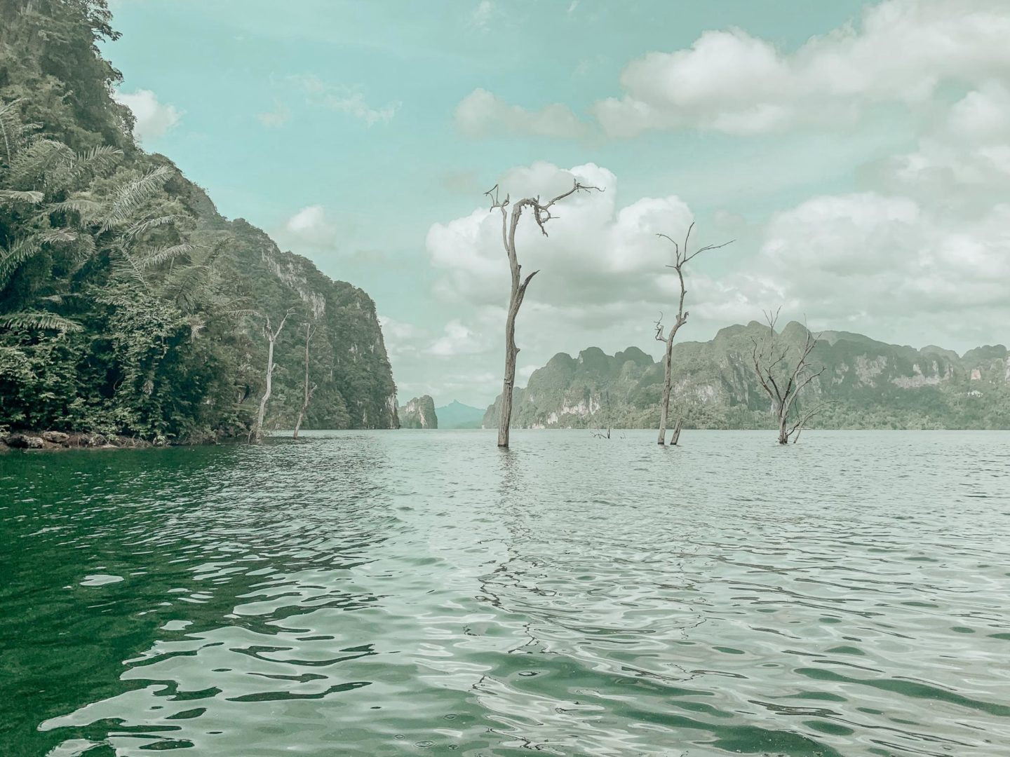 Forest remnants at Cheow Lan Lake can be see above the emerald green lake itself