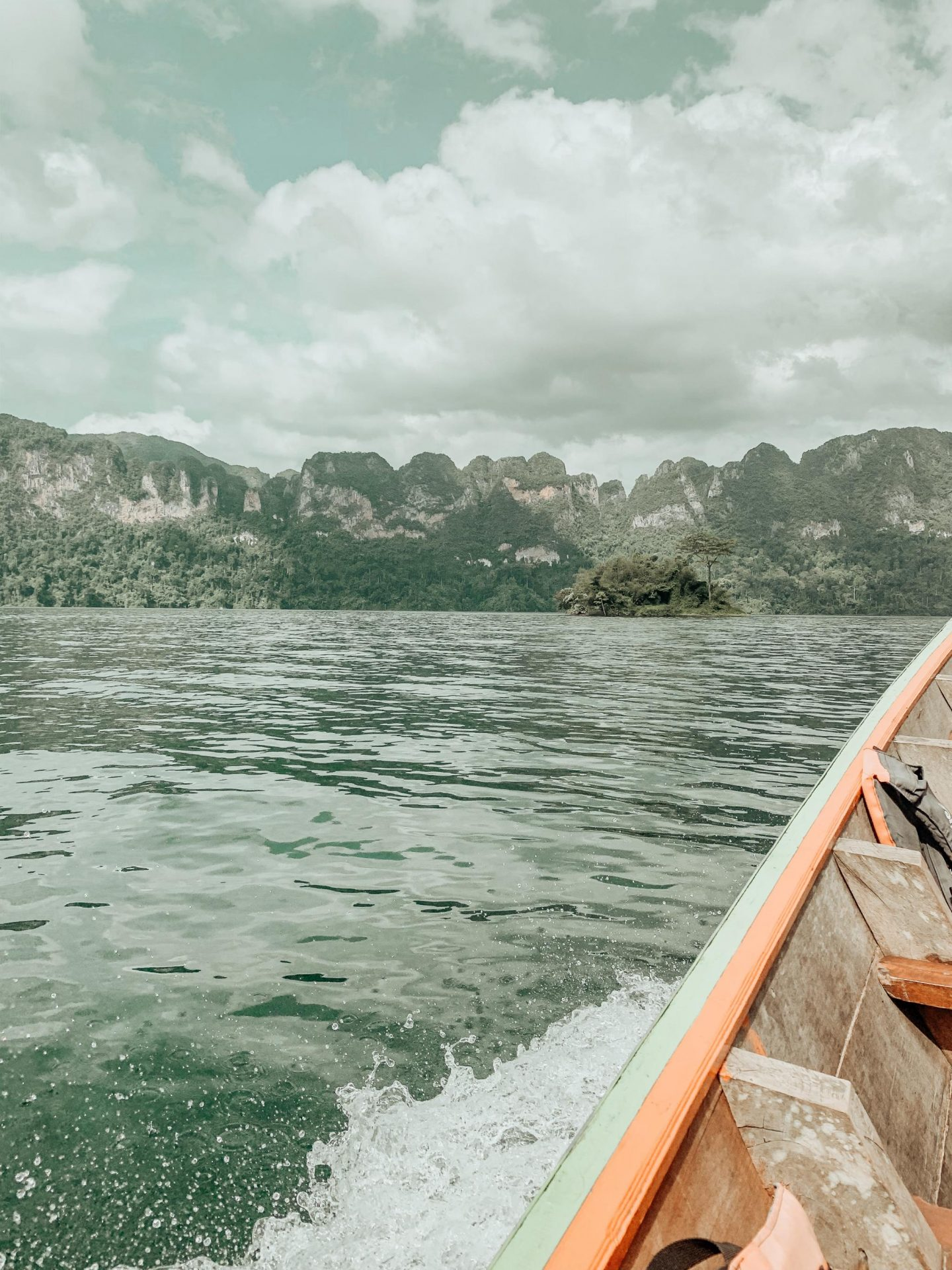 A traditional Thai long-tail boat on Cheow Lan Lake surrounded by limestone mountains